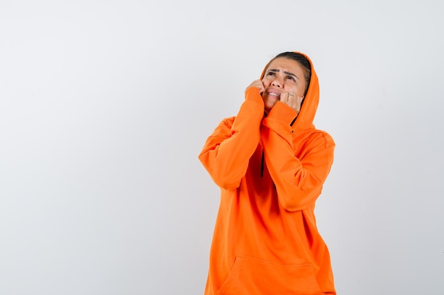 Giovane donna in felpa con cappuccio arancione che mette le mani sulle guance, guarda in alto e sembra tormentata