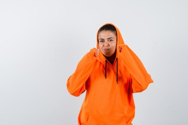 Giovane donna in felpa con cappuccio arancione in piedi in posa da pugile e bellissima