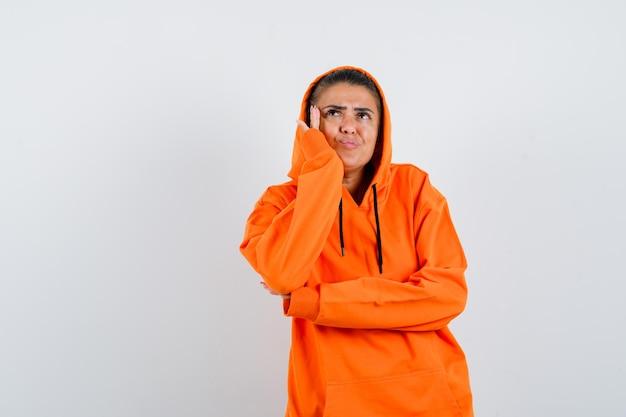 Giovane donna in felpa con cappuccio arancione in piedi in posa di pensiero e guardando pensierosa