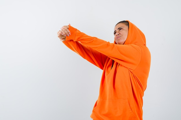 Giovane donna in felpa con cappuccio arancione che allunga le mani e sembra bellissima
