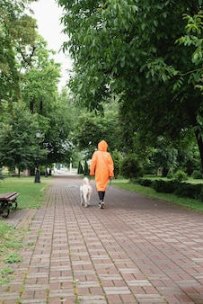Young woman in orange raincoat walking with her dog in a park