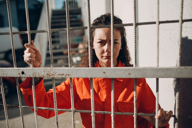 Young woman in orange suit behind jail bars female in colorful overalls portrait law and justice concept