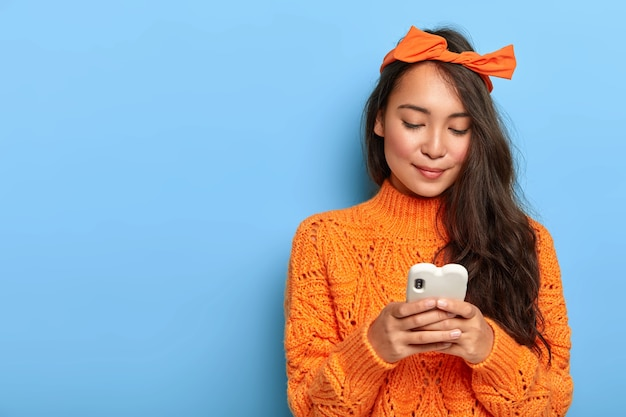Young woman in orange sweater chatting on her smartphone