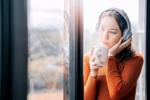 Young woman in orange sweater listening musice and holding cup while standing by window and looking outside.