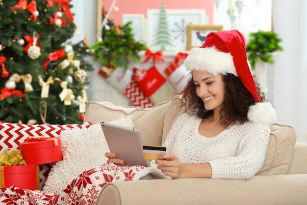 온라인으로 크리스마스 선물을 주문하는 젊은 여성