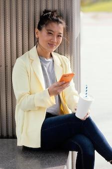 コーヒーを楽しんで屋外で若い女性