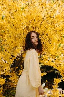 黄色い花の背景を持つ茂みの庭で屋外の若い女性