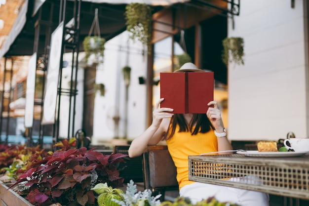 Young woman in outdoors street coffee shop cafe sitting at table in hat, covering face behind red book hiding, relaxing in restaurant during free time