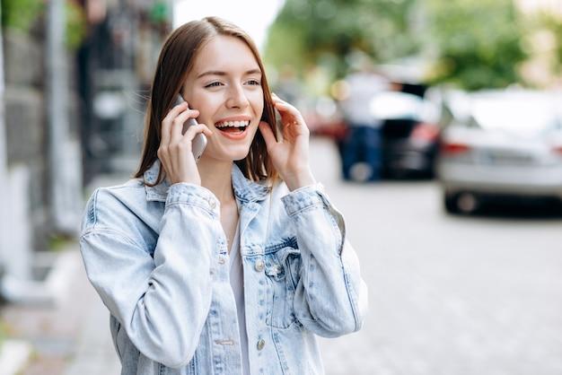 電話で屋外で話している若い女性