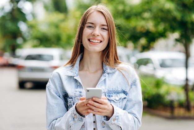 電話を使用して屋外で若い女性