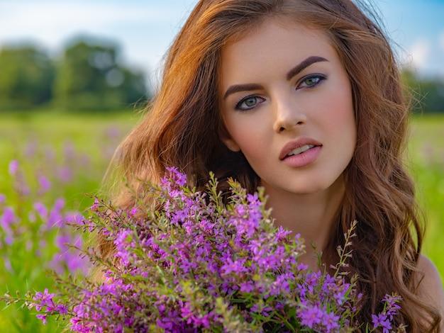 花束を持つ屋外の若い女性。彼女の手にラベンダーの花を持つフィールドの女の子。自然の白人女性のクローズアップの肖像画。
