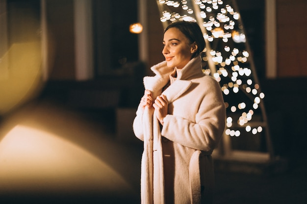Young woman outside the night street with lights