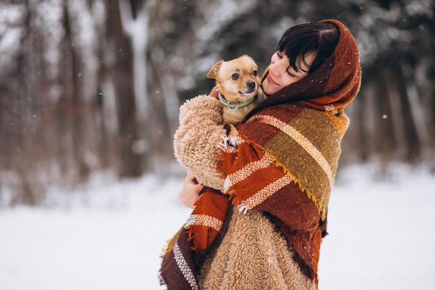 Young woman outside the park with her little dog at winter