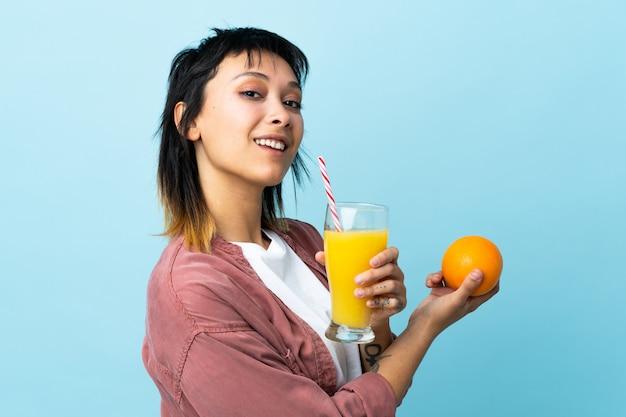 オレンジとオレンジジュースを保持している青い壁の上の若い女性
