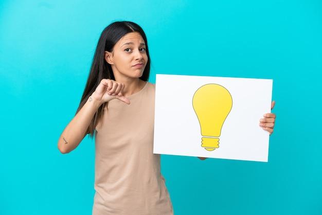 電球のアイコンが付いたプラカードを保持し、それを指している孤立した背景上の若い女性