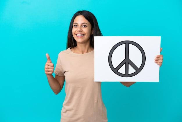 Молодая женщина на изолированном фоне держит плакат с символом мира с большим пальцем вверх