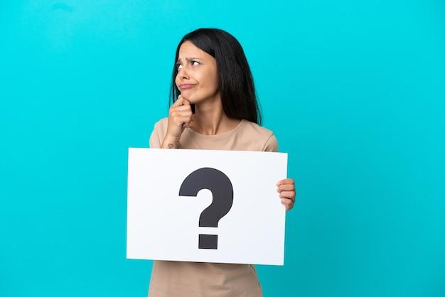 Молодая женщина на изолированном фоне держит плакат с символом вопросительного знака и думает