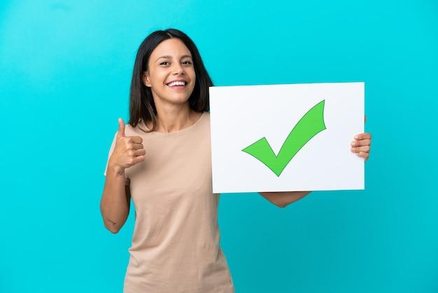 テキストとプラカードを保持している孤立した背景上の若い女性親指を上に緑のチェックマークアイコン