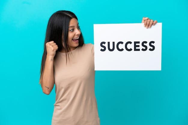 Молодая женщина на изолированном фоне держит плакат с текстом успех и празднует победу