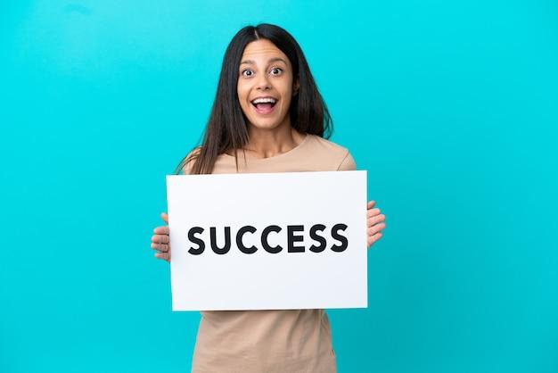 Молодая женщина на изолированном фоне держит плакат с текстом успех с удивленным выражением лица