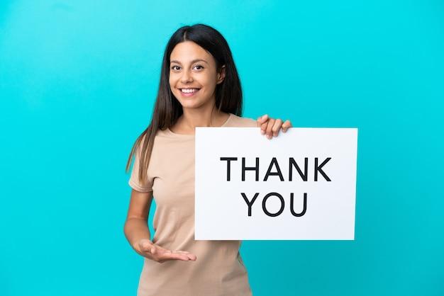 Молодая женщина на изолированном фоне держит плакат с текстом спасибо и указывает на него