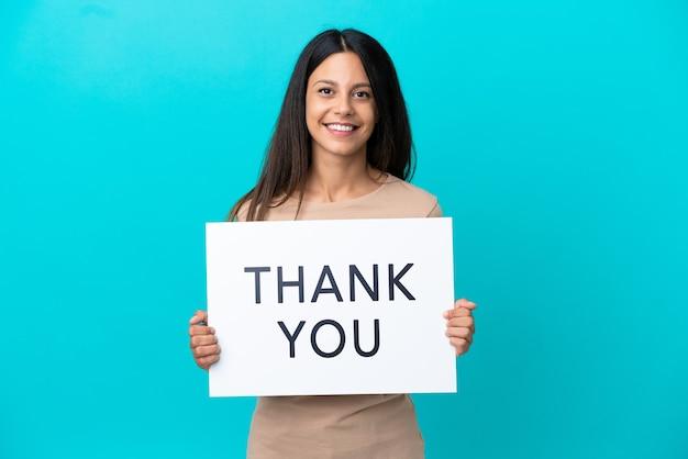Молодая женщина на изолированном фоне держит плакат с текстом спасибо с счастливым выражением лица