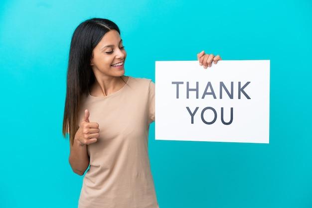 Молодая женщина на изолированном фоне держит плакат с текстом спасибо с большим пальцем вверх