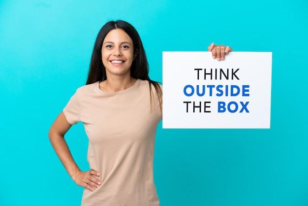격리된 배경 위에 있는 젊은 여성이 행복한 표정으로 Think Outside The Box라는 문구가 적힌 플래카드를 들고 있습니다. 프리미엄 사진