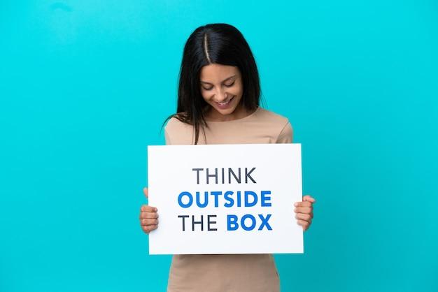 격리된 배경 위에 있는 젊은 여성이 think outside the box라는 문구가 적힌 플래카드를 들고 있습니다.