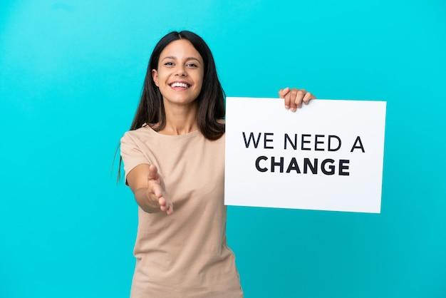 격리된 배경 위에 있는 젊은 여성이 거래를 하는 우리에게 변화가 필요합니다.라는 문구가 적힌 플래카드를 들고 있습니다.