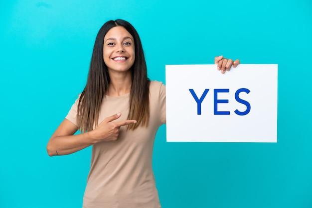 격리된 배경 위에 있는 젊은 여성이 yes라는 문구가 적힌 플래카드를 들고 그것을 가리키는