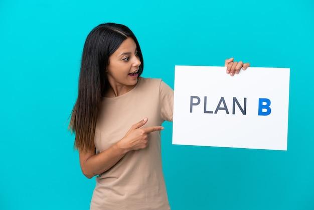 Молодая женщина на изолированном фоне держит плакат с сообщением план b с удивленным выражением лица
