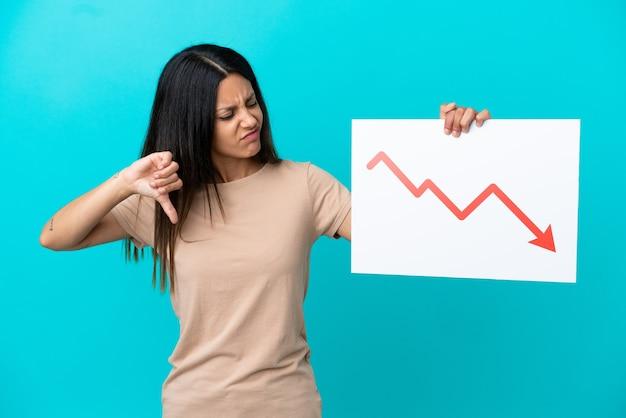 Молодая женщина на изолированном фоне держит табличку с символом стрелки убывающей статистики и делает плохой сигнал