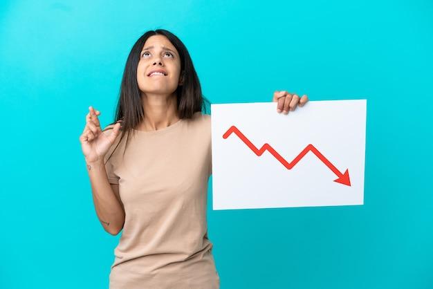 Молодая женщина на изолированном фоне с табличкой с уменьшающейся статистикой стрелкой со скрещенными пальцами