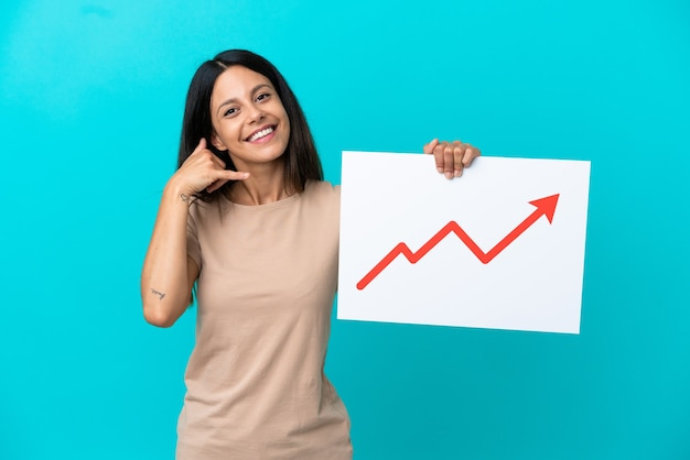 Молодая женщина на изолированном фоне держит табличку с растущим символом стрелки статистики и делает жест по телефону