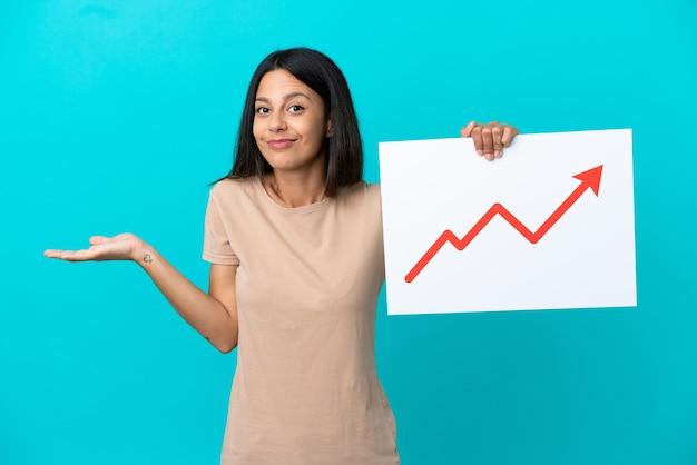 Молодая женщина на изолированном фоне держит знак с растущим символом стрелки статистики, имеющим сомнения