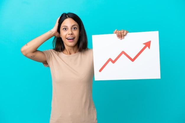 놀란 표정으로 성장하는 통계 화살표 기호가 있는 표지판을 들고 고립된 배경 위에 있는 젊은 여성