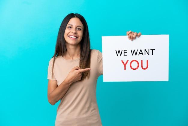 Молодая женщина на изолированном фоне держит доску мы хотим, чтобы ты и указывая на нее