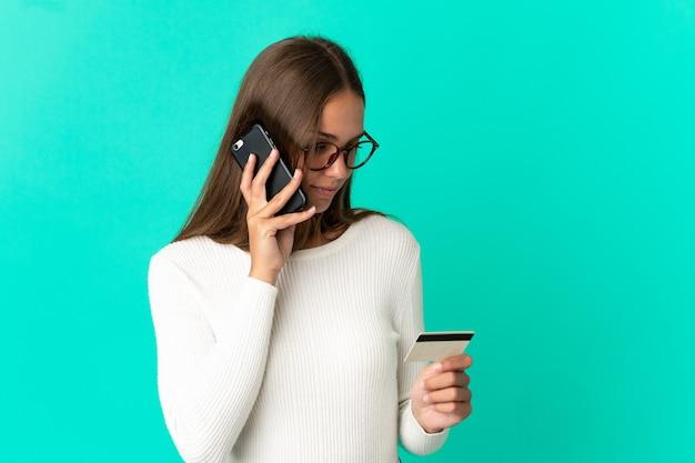 Молодая женщина на изолированном синем фоне покупает с мобильного с помощью кредитной карты