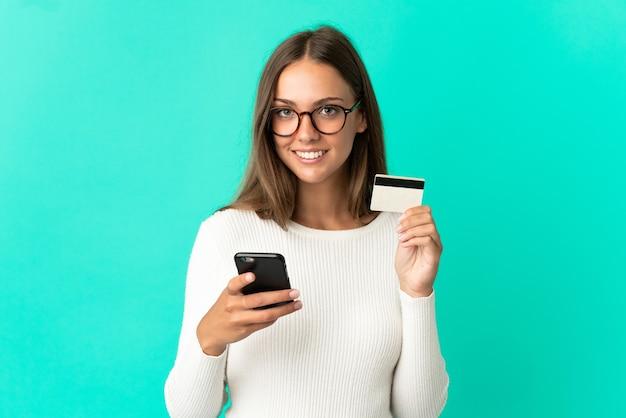 Молодая женщина на изолированном синем фоне покупает с мобильного телефона с помощью кредитной карты