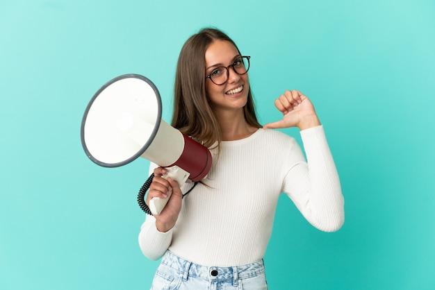 Молодая женщина на изолированном синем фоне держит мегафон и гордая и самодовольная