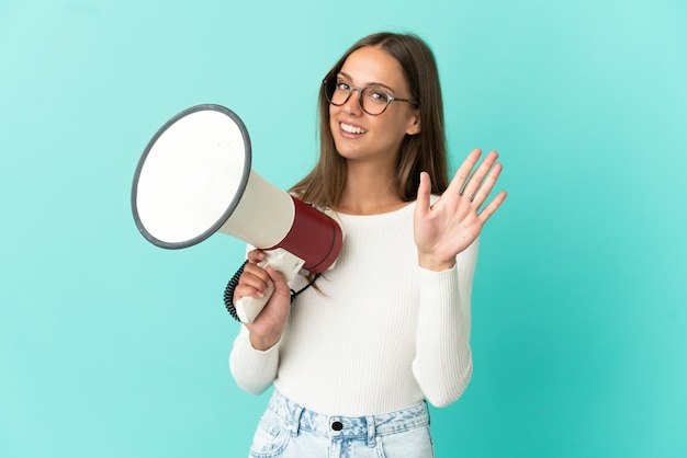 Молодая женщина на изолированном синем фоне держит мегафон и салютует рукой с счастливым выражением лица