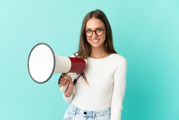 Молодая женщина на изолированном синем фоне держит мегафон и много улыбается