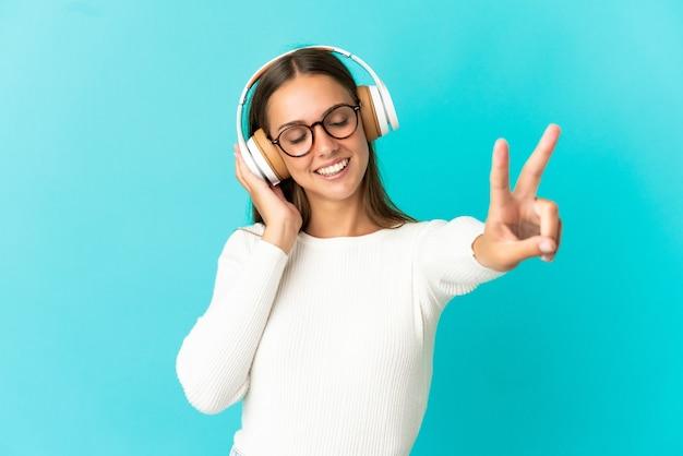 Молодая женщина на изолированном синем фоне слушает музыку и поет