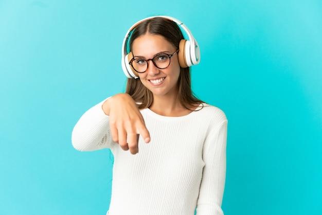 音楽を聞いて孤立した青い背景の上の若い女性
