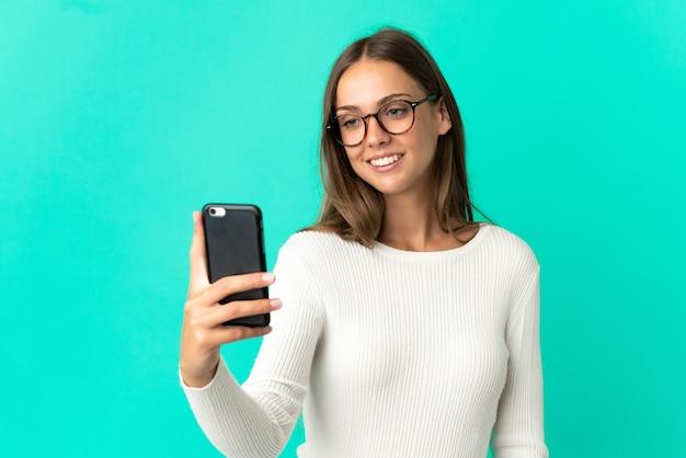 Молодая женщина на изолированном синем фоне, делая селфи с мобильным телефоном