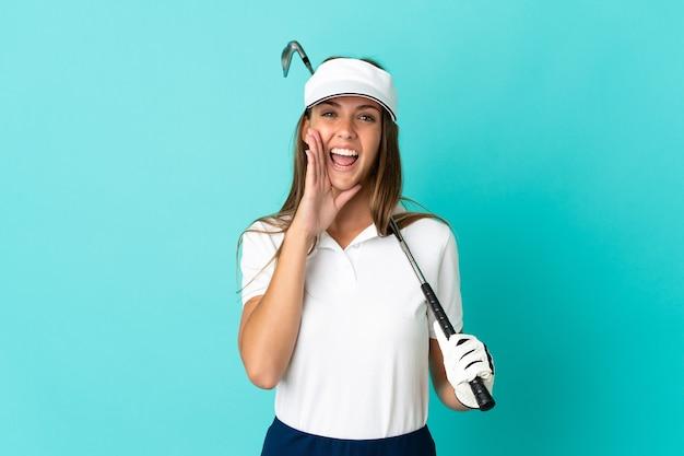 Молодая женщина на изолированном синем фоне играет в гольф и кричит с широко открытым ртом
