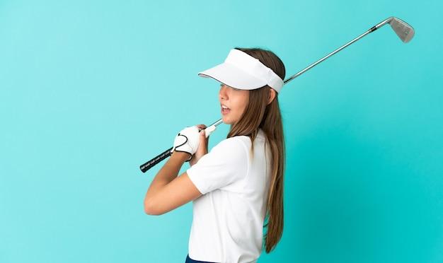 Молодая женщина на изолированном синем фоне играет в гольф
