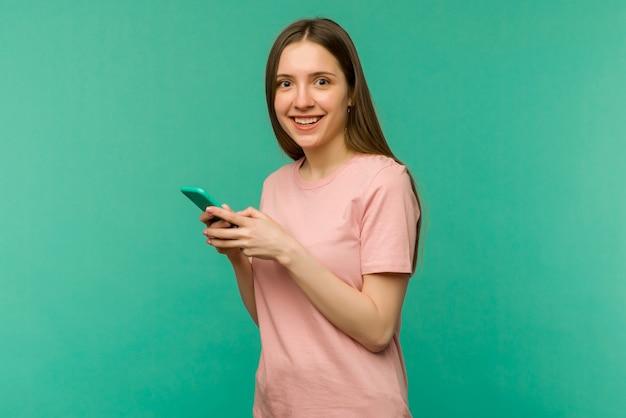 놀란 및 메시지를 보내는 격리 된 파란색 배경 위에 젊은 여자