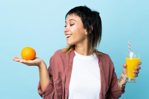 オレンジとオレンジジュースを保持している孤立した青以上の若い女性